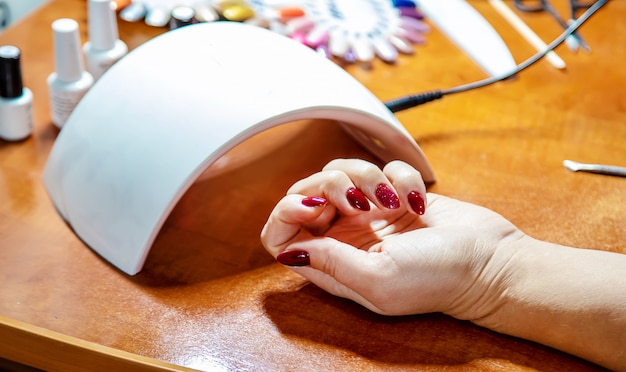Manicure at home, gel polish, dry in the lamp. selective focus.