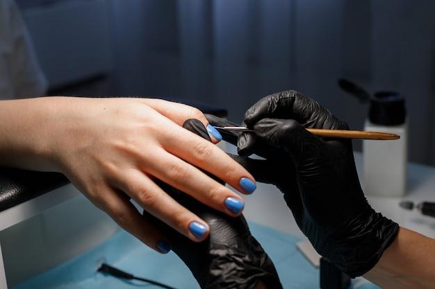 살롱 근접 촬영에 매니큐어 여자는 매니큐어로 손톱을 페인트