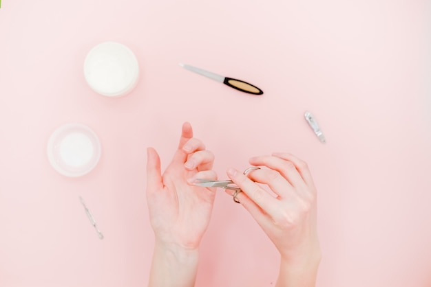 Manicure kit, scisors, polisher. skin care concept. light pink abstract background.