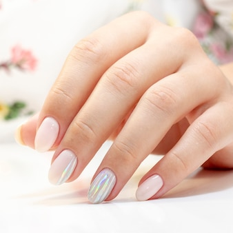 Manicure. the manicurist made a manicure and gel polish on the clients nails in gentle tones with stripes of foil gloss