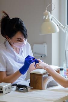 Manicure master applying a nail polish