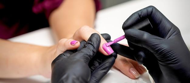 Мастер маникюра наносит розовый лак для ногтей