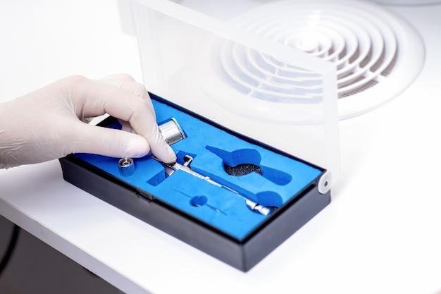 Рука мастера маникюра достает аэрограф для ногтей в белых перчатках из коробки.