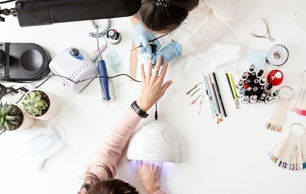 Мастер маникюра в маске и перчатках наносит гель-лак на ногти клиента.