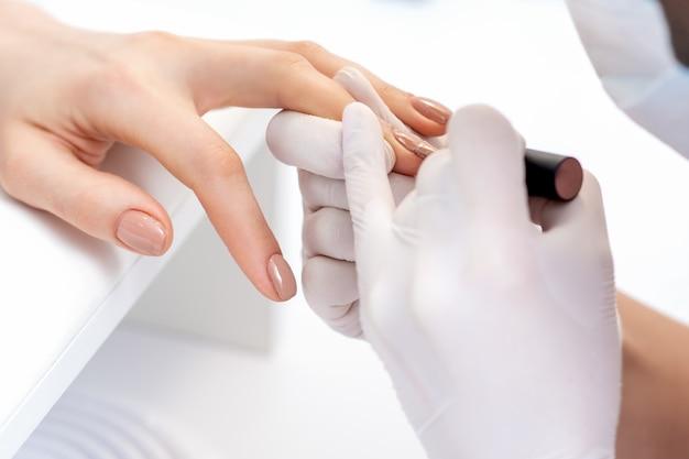 ビューティーサロンで女性の爪にベージュのマニキュアを適用する保護手袋のマニキュアマスター