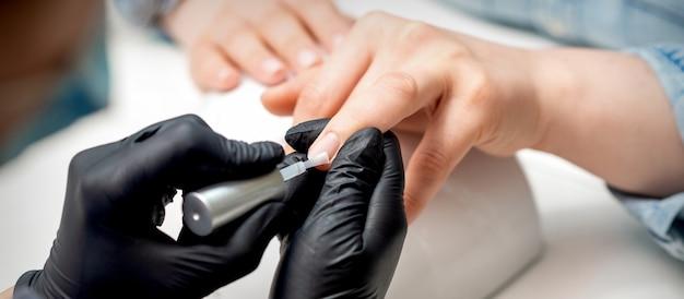 マニキュアマスターがネイルサロンで女性の爪に透明なニスを塗っています