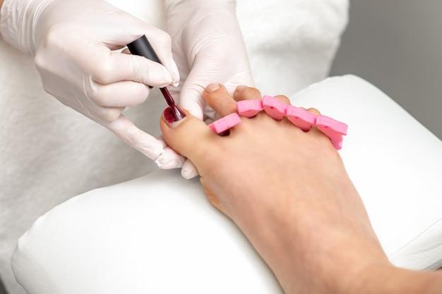 Мастер маникюра красит женские ногти на ногах бордовым лаком кистью в белых перчатках.