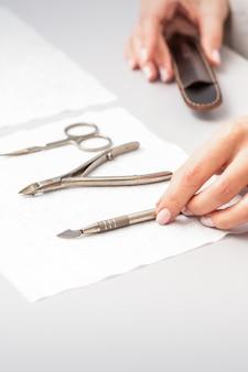 マニキュアマスターは、ネイルサロンのテーブルでタオルにセットされたマニキュアをレイアウトします
