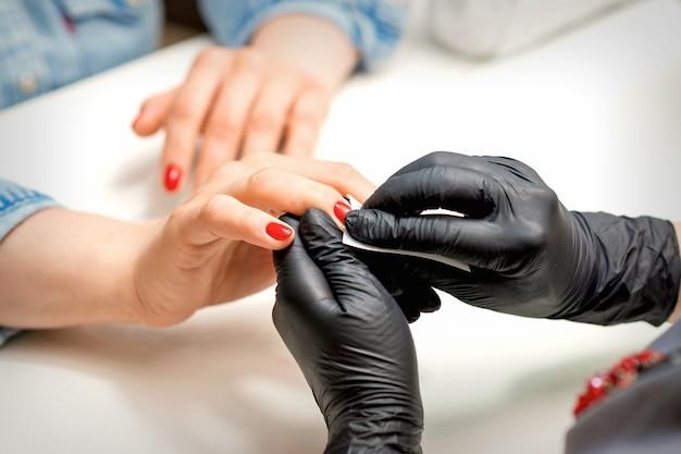 매니큐어 마스터는 네일 살롱에서 냅킨으로 여성 빨간 손톱을 누출합니다.