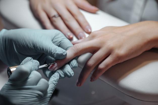 マニキュアマスターは美容院で爪をかわいいかわいい若い女性にします。素晴らしいイメージを作成するためのインテリアサロンでのカスタマーサービス。作品作成ウィザード。測定満足度の概念。コピースペース