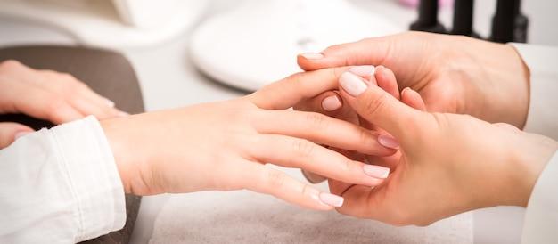 네일 살롱에서 네일 폴리싱 후 클라이언트 여성 손가락을 마사지하는 매니큐어 마스터