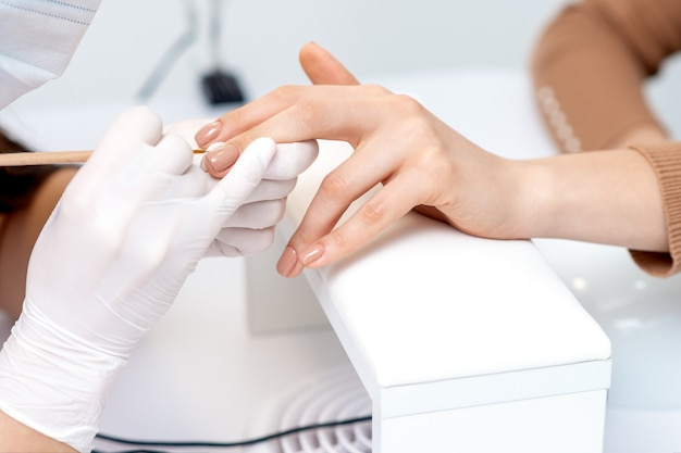 Manicure master in protective gloves applying beige nail polish on female nails in beauty salon
