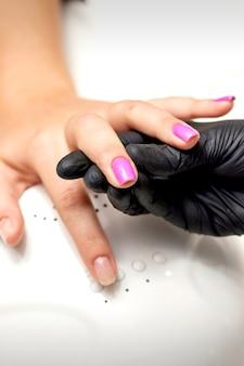 ネイルサロンでネイルを塗っている間、マニキュアマスターの手は紫色のマニキュアで女性の指を持っています