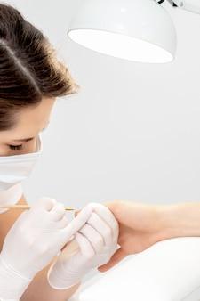 ビューティーサロンで女性の爪にベージュのマニキュアを適用するゴム手袋の保護マスクを持つマニキュアマスター
