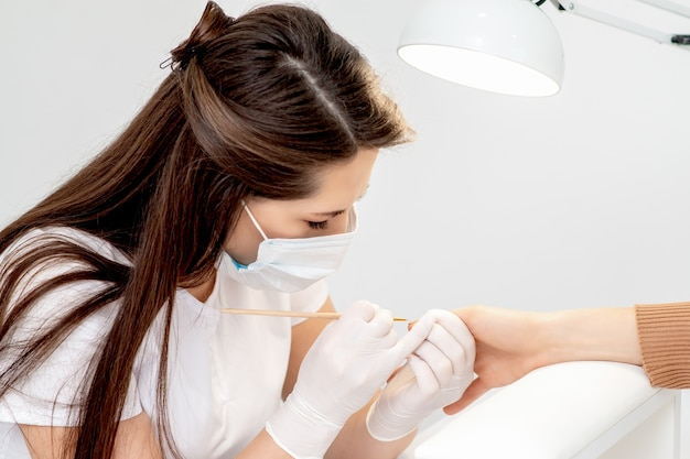 Manicure master with protective mask in rubber gloves applying beige nail polish on female nails in beauty salon
