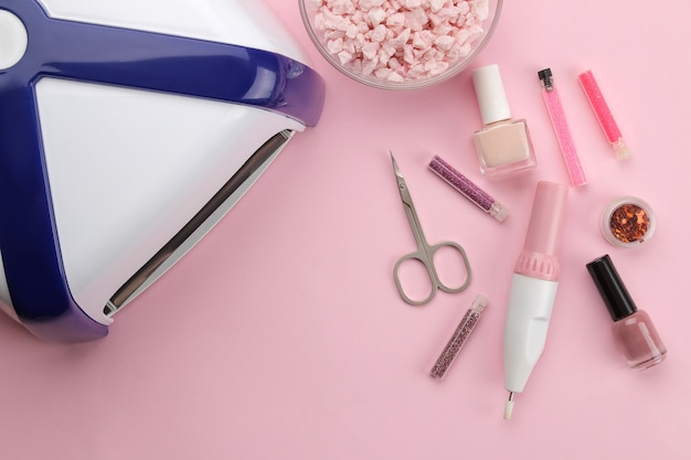 Manicure. nail polishes, uv lamp and various accessories and tools for manicure on a trendy pink background. top view