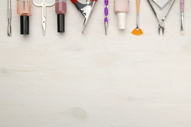 Manicure. nail polishes and various accessories and tools for manicure on a white wooden table. top view