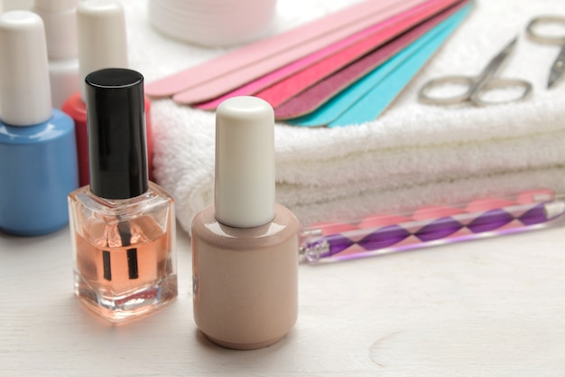 Manicure. nail polishes and various accessories and tools for manicure on a white wooden table