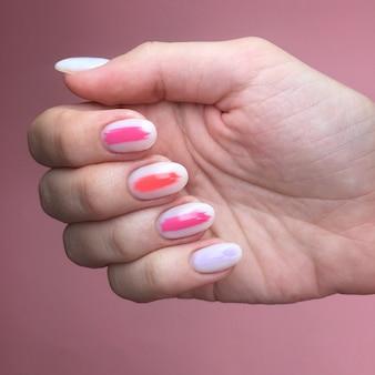 爪のさまざまな色のマニキュア。ピンクの背景の手に女性のマニキュア