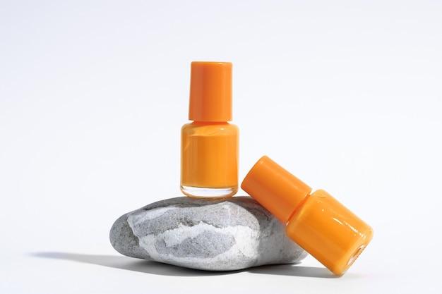 マニキュアまたはペディキュアの背景。オレンジ色のマニキュア、石、白い背景の上の孤立した化粧品ボトルの創造的なモックアップ。