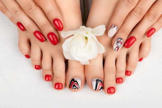 Manicure pedicure beauty salon concept womans feet and hands on gray