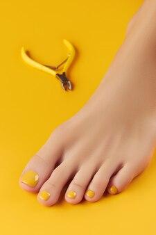 Маникюр, педикюр, салон красоты, концепция женской ноги с кусачками на оранжевом фоне