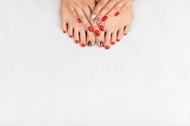 Маникюр, концепция салона красоты педикюра. женские руки и ноги на сером