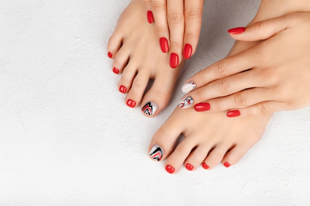 Manicure, pedicure beauty salon concept. womans hands and feet on gray