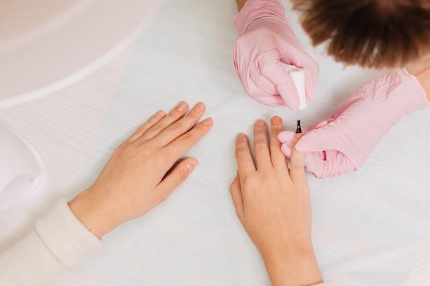 Процесс маникюра. мастер красит ногти прозрачным лаком.