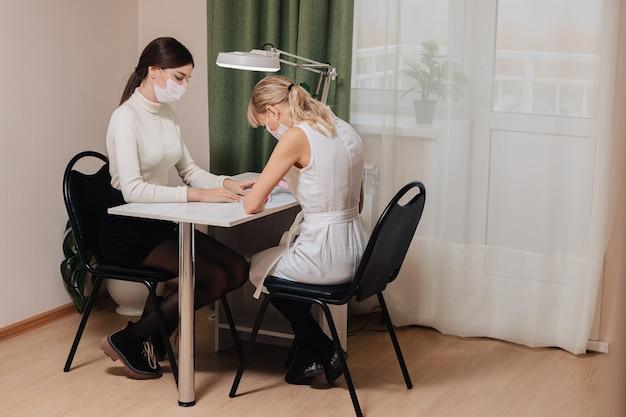 Процесс маникюра. работа на дому. мастер делает маникюр. две женщины в медицинских масках.