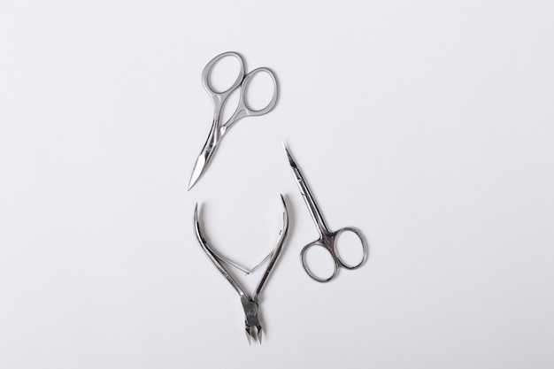 Manicure scissors and forceps for manicure on a white table