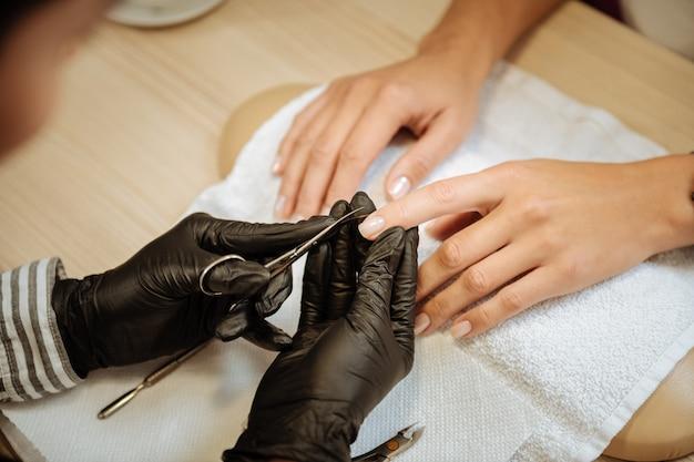 Ножницы маникюрные. вид сверху профессионального мастера по маникюру, держащего маникюрные ножницы во время оказания услуг клиенту
