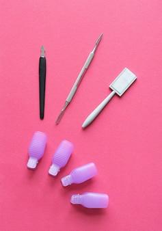 ピンクの背景に綿棒でシェラックのマニキュアセットをクローズアップ