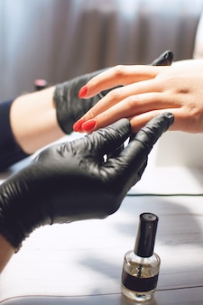 Manicure specialist in black gloves cares about nails