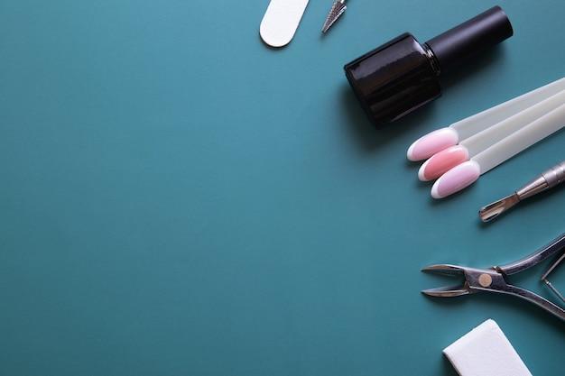 Инструменты и советы для маникюра на синем фоне с копией пространства. концепция покрытия гель-лаком