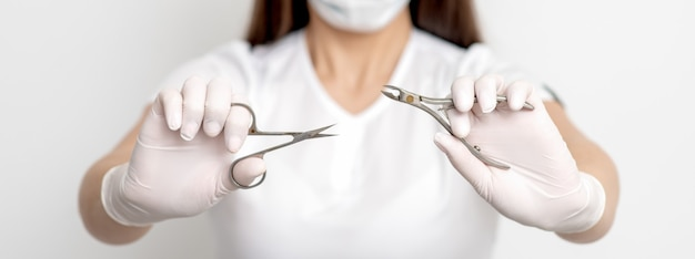 Manicure tools in hands of female manicurist wearing white mask and gloves on white wall