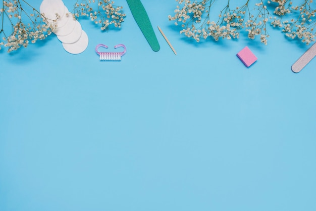 파란색 배경에 매니큐어 도구는 흰색 안개꽃으로 장식되어 있습니다.