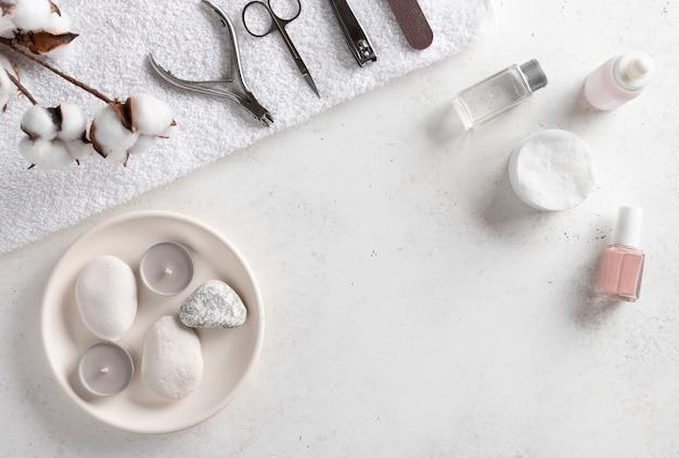 Маникюрные инструменты на белом банном полотенце, жидкость для снятия лака, масло для кутикулы и обнаженный лак для ногтей. рамка-бордюр для салона красоты. белая бетонная стена с копией пространства.