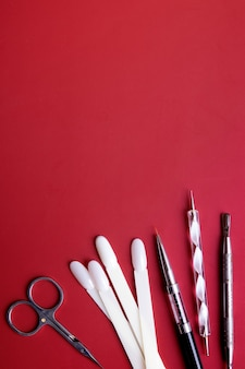 Manicure tools and tips for nail art on red background with copy space. gel polish coating concept