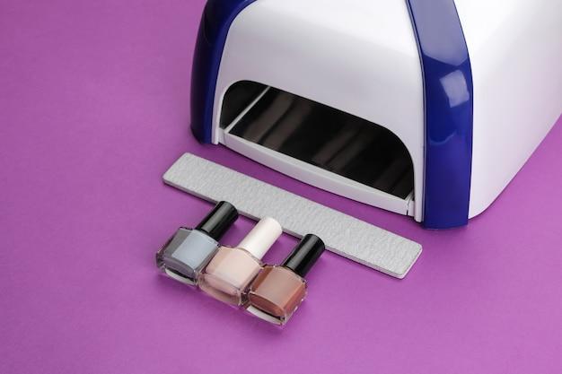 Маникюр. уф-лампа, пилочки и лаки для ногтей на модном фиолетовом фоне. маникюрные аксессуары и инструменты для ногтей.