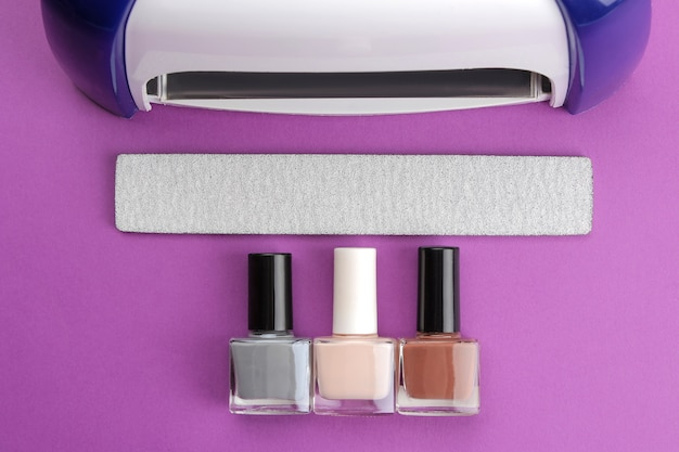 Manicure. uv lamp and nail files and nail polishes on a trendy purple background. manicure accessories and tools for nails. top view