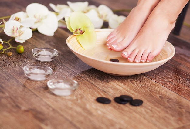 Manicured female feet in spa wooden bowl with flowers and water closeup
