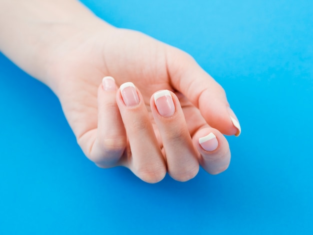 Manicured hand on blue background