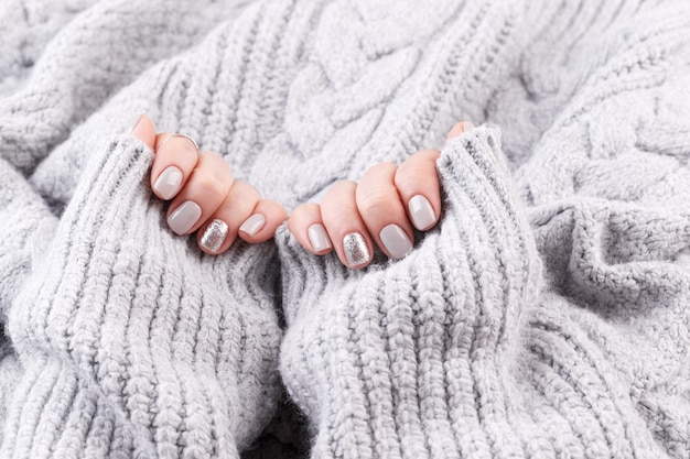 Manicured woman hands, grey knitted background, close up