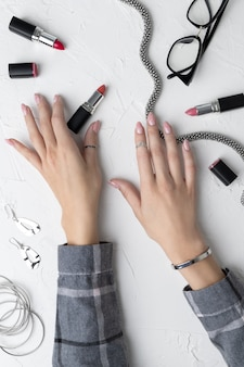 Manicured woman hands in trendy gray shirt with cosmetics and accessories