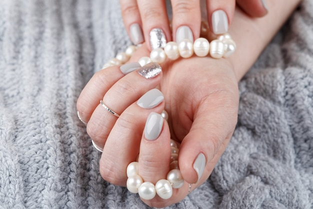 Manicured woman hands with pastel nail polish holding natural pearls, grey knitted background, close up