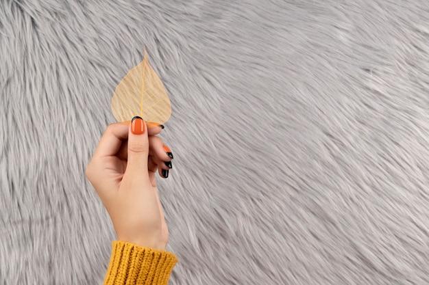 灰色のふわふわに黄色の葉を持っている手入れの行き届いた女性の手