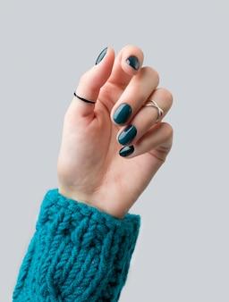 Ухоженная женская рука в теплой шерстяной бирюзовой поте