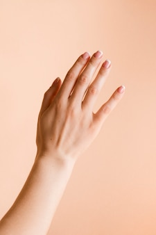 Manicured woman's hand on pale orange background