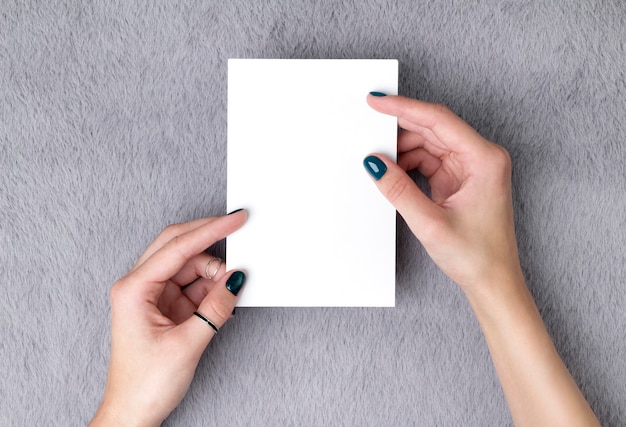 Manicured woman's hands holding postcard on grey furry table